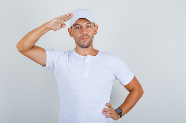 Young man saluting with hand on waist in white t-shirt, cap front view.