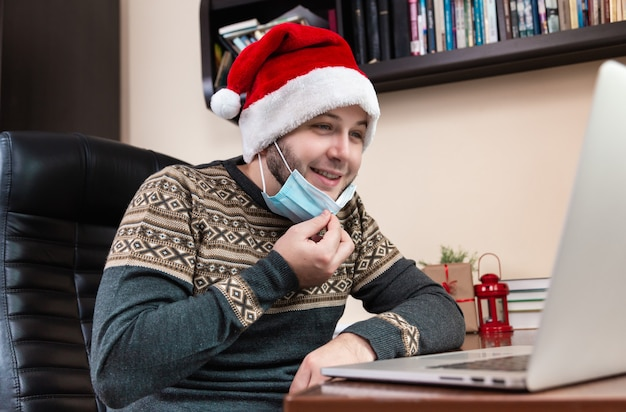 Young man in santa claus hat and face mask talks using laptop for video call friends and childrens. christmas during coronavirus.