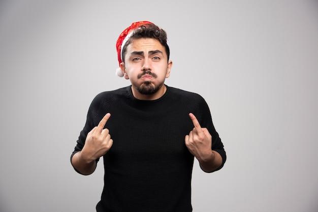 Un giovane uomo con il cappello rosso di babbo natale che punta a se stesso. foto di alta qualità