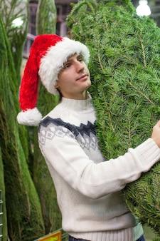 Young man in santa hat buying christmas tree
