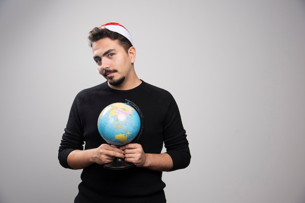 Young man in santa's hat holding a globe.