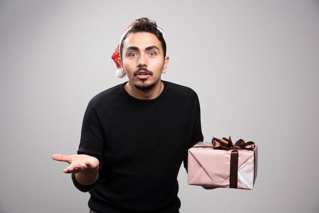 Un giovane uomo con il cappello di babbo natale che tiene un regalo di capodanno.