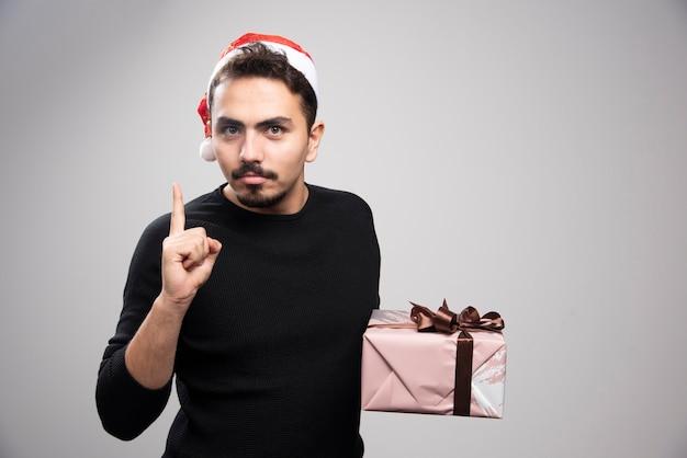 Un giovane con un cappello da babbo natale che mostra un dito e tiene un regalo.