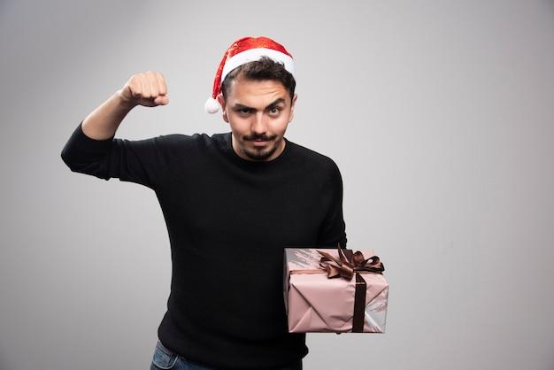 Un giovane con un cappello da babbo natale che mostra i suoi muscoli e che tiene un regalo.