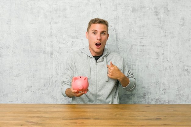 Young man saving money with a piggy bank surprised pointing with finger, smiling broadly.