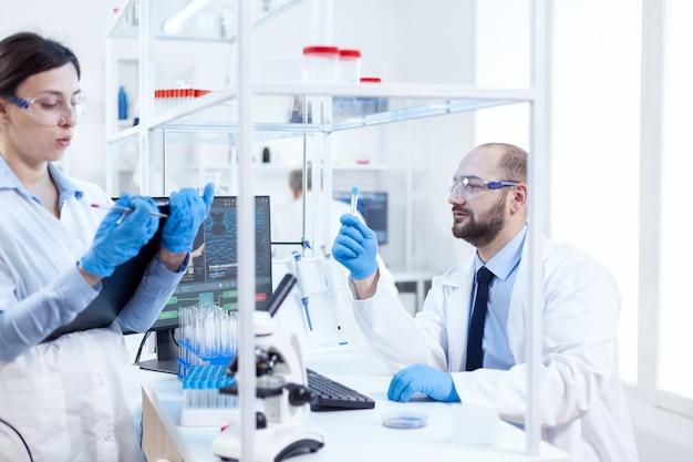 Ученый молодой человек смотрит задумчиво на химический раствор в пробирках. команда химиков-химиков, работающих вместе в стерильной микробиологической лаборатории, проводит исследования.