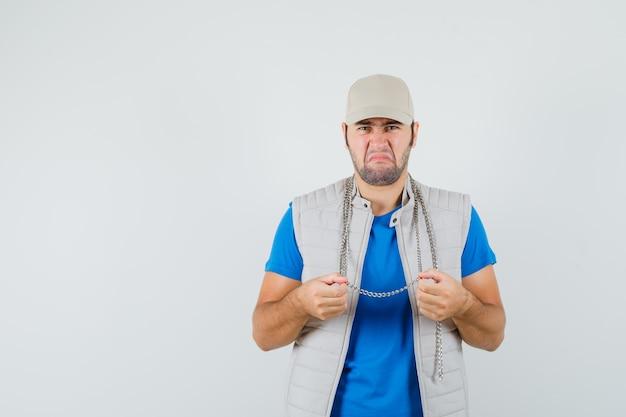 Tシャツ、ジャケット、キャップの正面図でチェーンネックレスを保持しながらしゃがむ若い男。