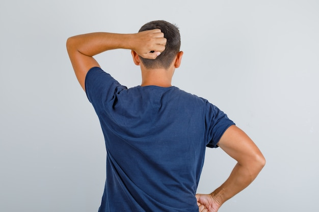 Young man scratching his head in dark blue t-shirt, back view.