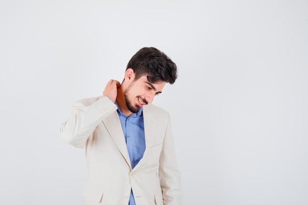 青いシャツと白いスーツのジャケットで首を引っ掻いて幸せそうに見える若い男
