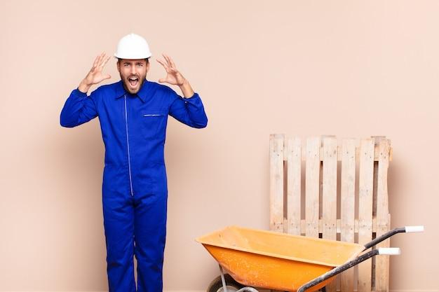 Молодой человек кричит в панике или гневе, шокирован, испуган или разъярен, с руками рядом с концепцией строительства головы