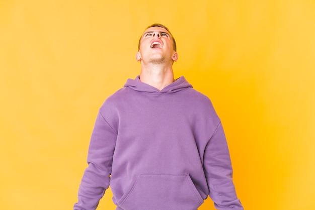 Молодой человек кричит, изолированные на желтом фоне