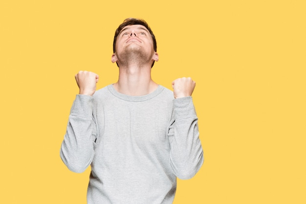 Young man screaming with delight on yellow studio background
