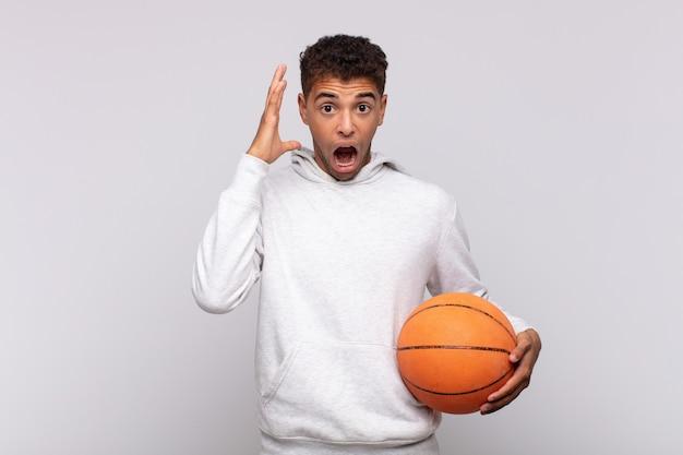 怒り、欲求不満、ストレス、動揺を感じて、空中で手を上げて叫んでいる若い男。バスケットコンセプト
