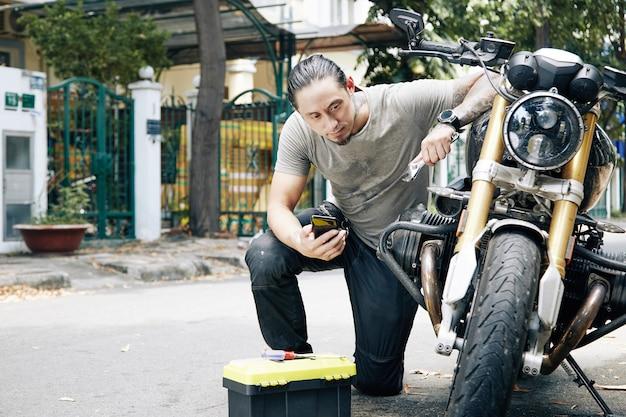 バイクを修理しようとすると、スマートフォンを介してオンラインで情報を検索する若い男