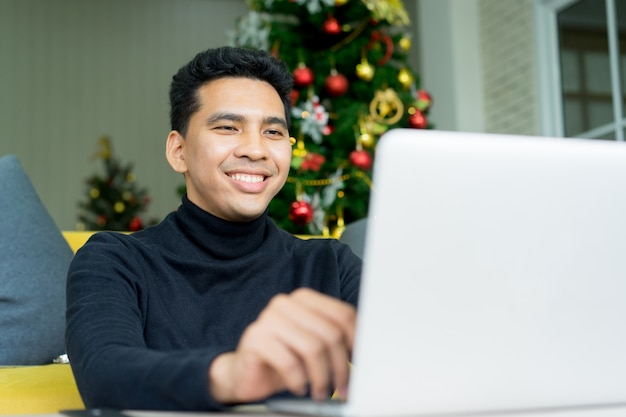 Young man searching website on laptop for shopping