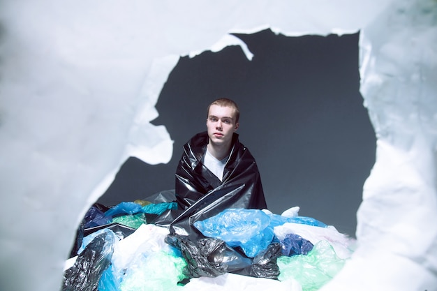 若い男が座って、ビニール袋のゴミ、暗い明るい背景で覆われています。