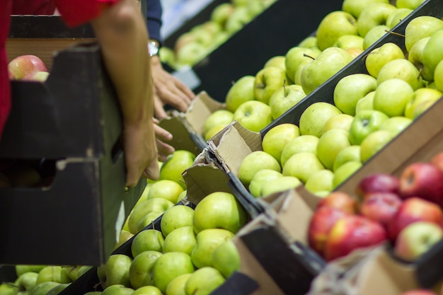 若い男の売り手は、食料品店で箱の新鮮な果物をレイアウトします。