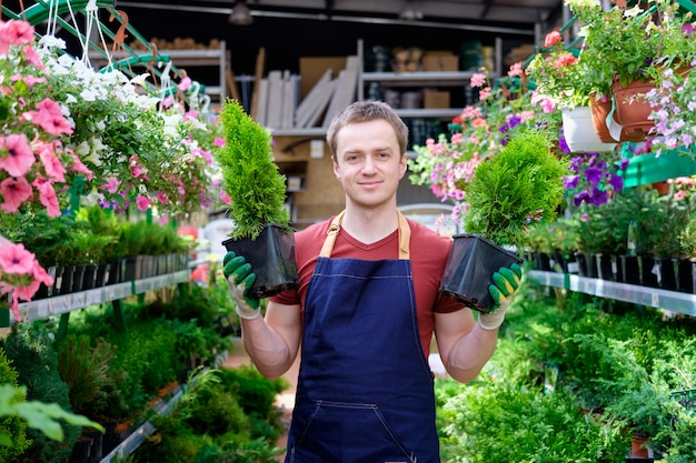 Young man seller in plant market greenhouse at work, florist