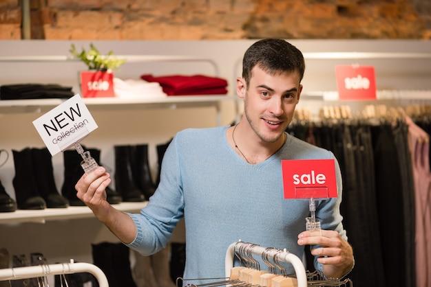 Молодой человек-продавец с красной распродажей и белыми бирками новой коллекции