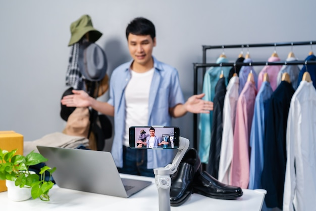 Young man selling clothes and accessories online by smartphone live streaming. business online e-commerce at home