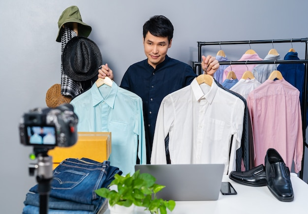 카메라 라이브 스트리밍으로 옷과 액세서리를 온라인으로 판매하는 젊은 남자. 가정에서의 비즈니스 온라인 전자 상거래