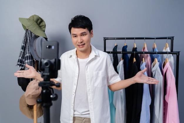 Молодой человек продает одежду и аксессуары онлайн с помощью смартфона в прямом эфире. интернет-магазин для бизнеса на дому