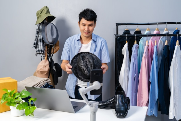 Young man selling hat and clothes online by smartphone live streaming. business online e-commerce at home