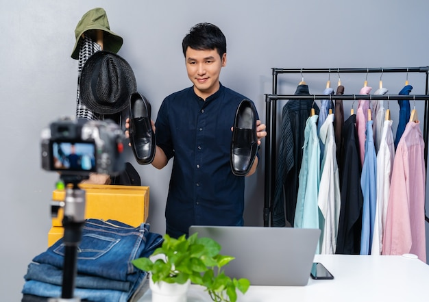 카메라 라이브 스트리밍으로 신발과 옷을 온라인으로 판매하는 젊은 남자. 가정에서의 비즈니스 온라인 전자 상거래