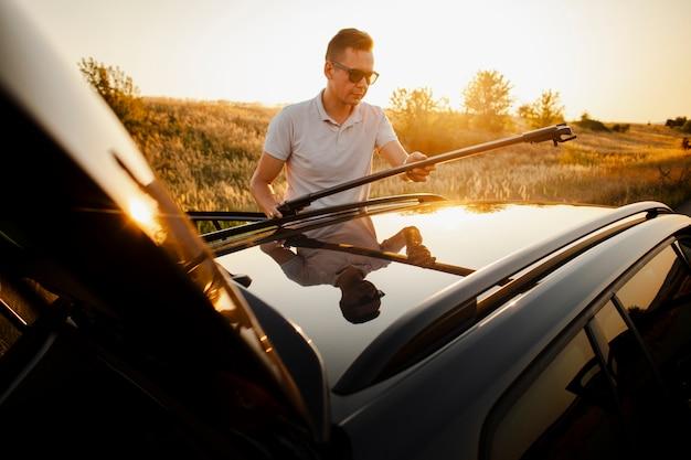 車の屋根をセットアップする若い男
