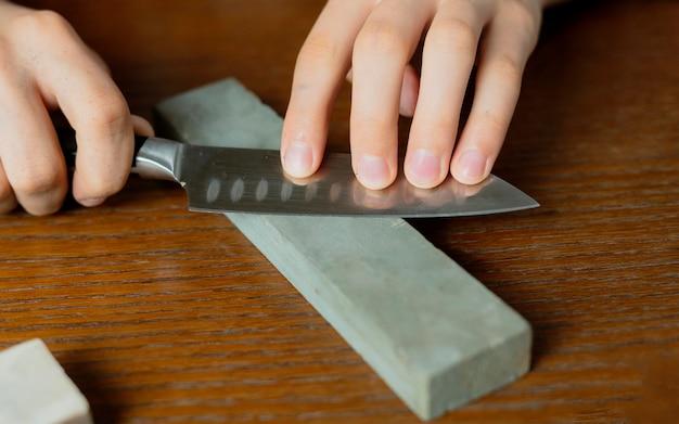 Молодой человек точит нож на деревянном столе на темном фоне b