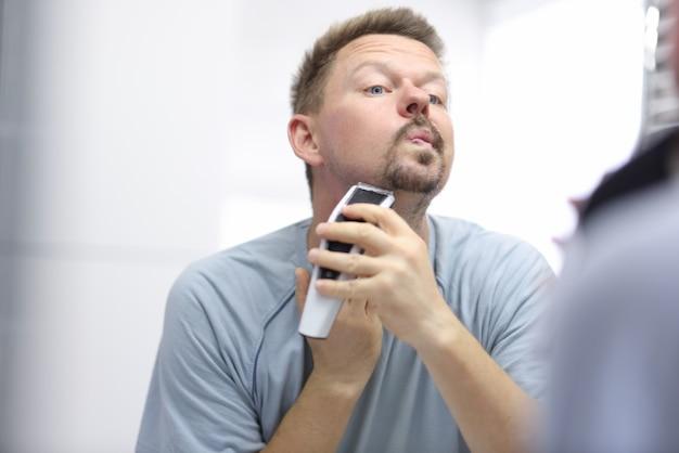 若い男は鏡を見ながらかみそりで顔を剃る