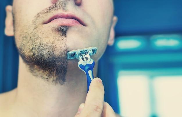 若い男は彼の短いあごひげシェービング工作機械を剃ります。ひげを半分剃った半分の顔。