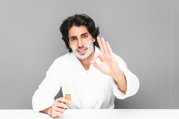 Young man shaving his beard cheerful and confident showing ok gesture.