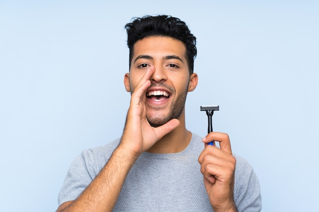 Young man shaving his beard shouting with mouth wide open