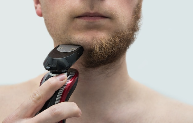 Young man shaving his beard with electric shaver. he shaved half of beard.