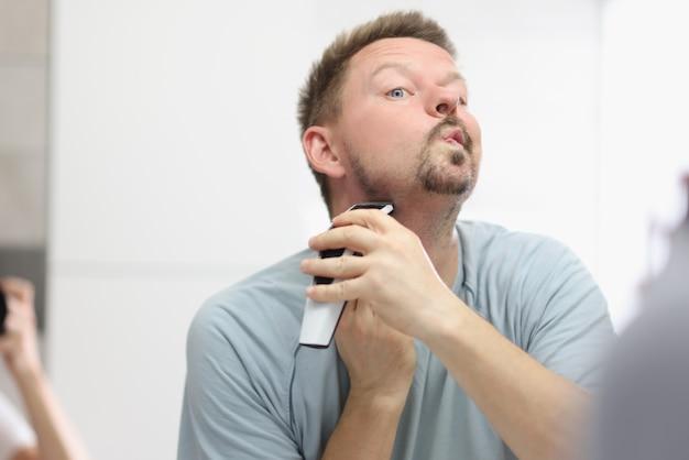 욕실에서 거울 앞에서 트리머로 그의 수염을 면도하는 젊은 남자