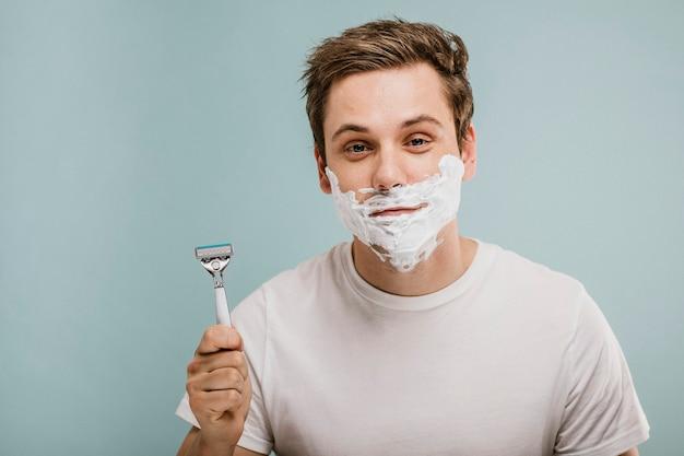 그의 수염을 면도하는 젊은 남자