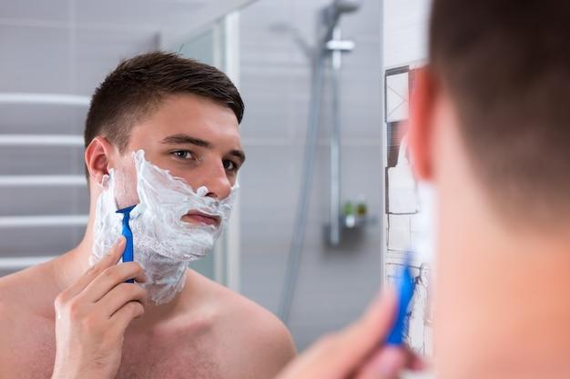 젊은 남자가 얼굴을 면도하고 집에 있는 현대적인 타일 욕실에서 거울을 보고 있다