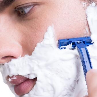 かみそりでひげを剃っている若い男-白で隔離