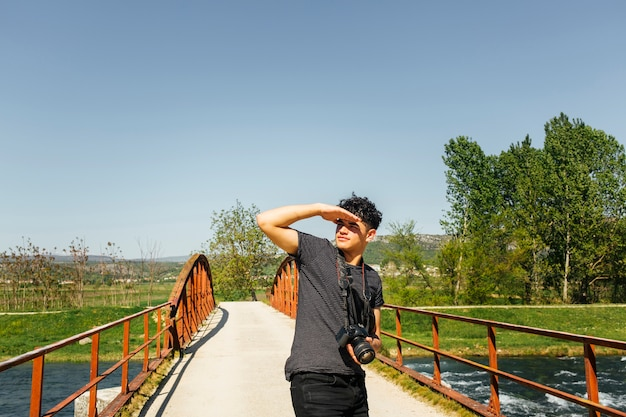 Young man shielding eye from sunlight with holding camera
