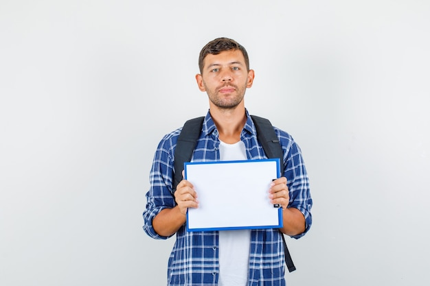 Young man in shirt, backpack holding clipboard and looking serious , front view.