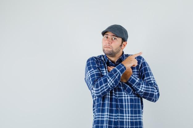 Giovane uomo in camicia, berretto tenendo la mano sul petto, indicando da parte e guardando ansioso, vista frontale.