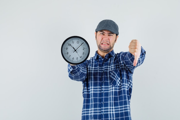 Young man in shirt, cap holding wall clock, showing thumb down and looking discontent , front view.