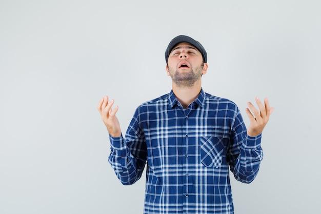 Giovane uomo in camicia, cappello alzando le mani nel gesto di preghiera e guardando speranzoso, vista frontale
