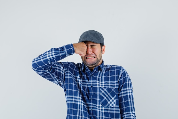 Young man in shirt, cap rubbing eye while crying and looking offended , front view.