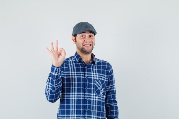 Giovane uomo in camicia, cappuccio che mostra gesto giusto e sembra allegro, vista frontale.
