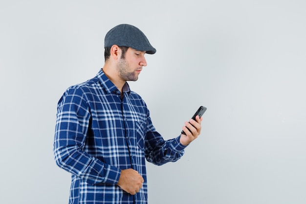 Young man in shirt, cap using mobile phone and looking busy , front view.