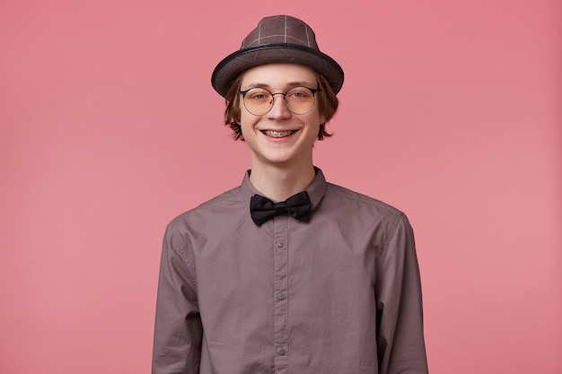 Young man in shirt hat and black bowtie wears glasses nice widely smiling showing orthodontic brackets isolated on pink background