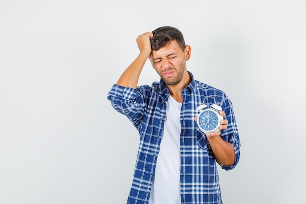 Young man in shirt holding alarm clock with hand on hair and looking regretful , front view.