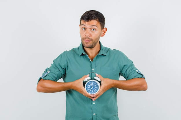 Young man in shirt holding alarm clock